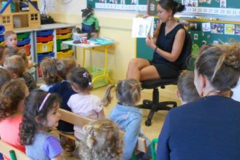 Les enfants de la crèche écoutent la maitresse lire un album